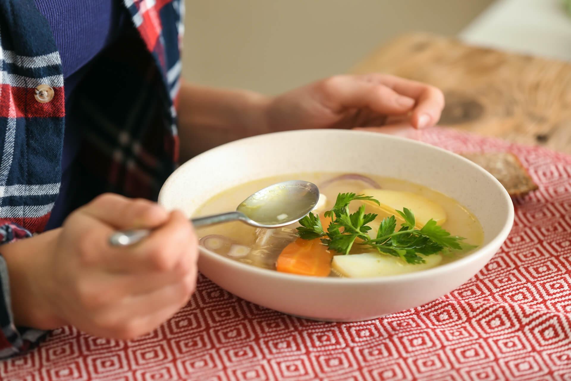 persona comiendo sopa de verduras