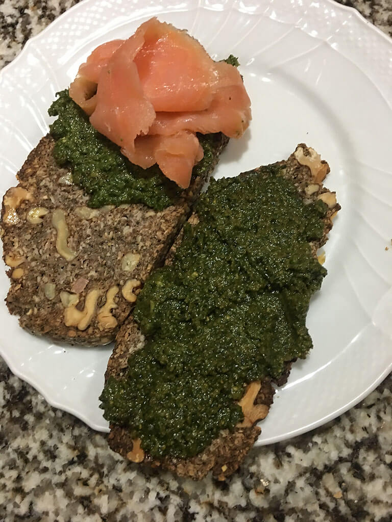 Rebanada de pan con pesto de albahaca y salmón ahumado