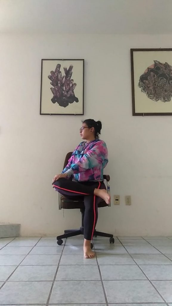 Woman doing yoga pose on chair