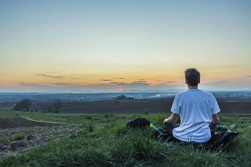 Man meditating infront of the sunset