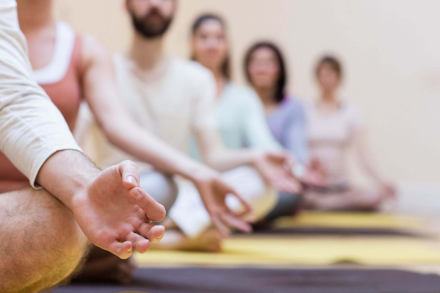 Group of people doing meditation on an exercise mat
