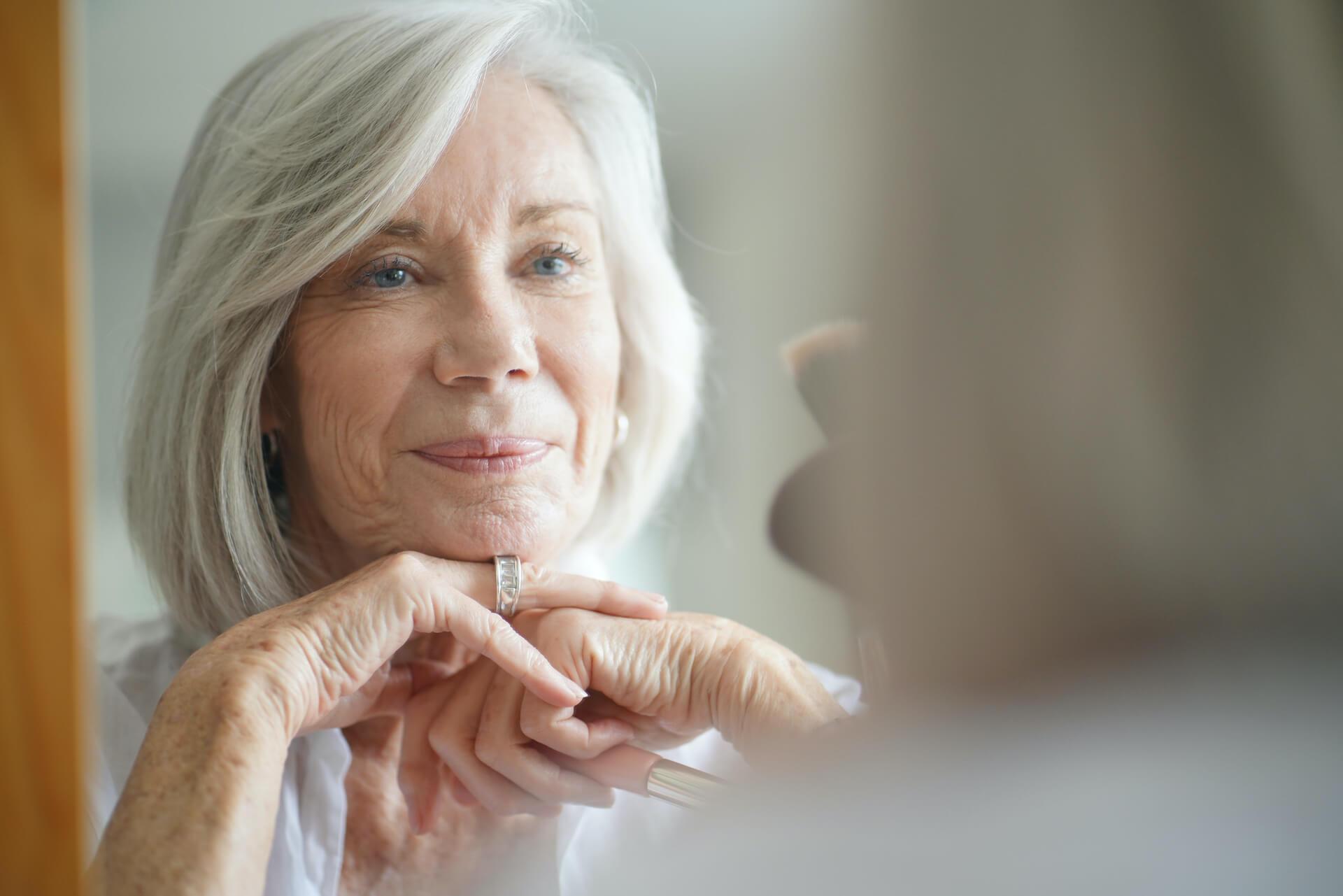 elder women looking at herself in a mirror