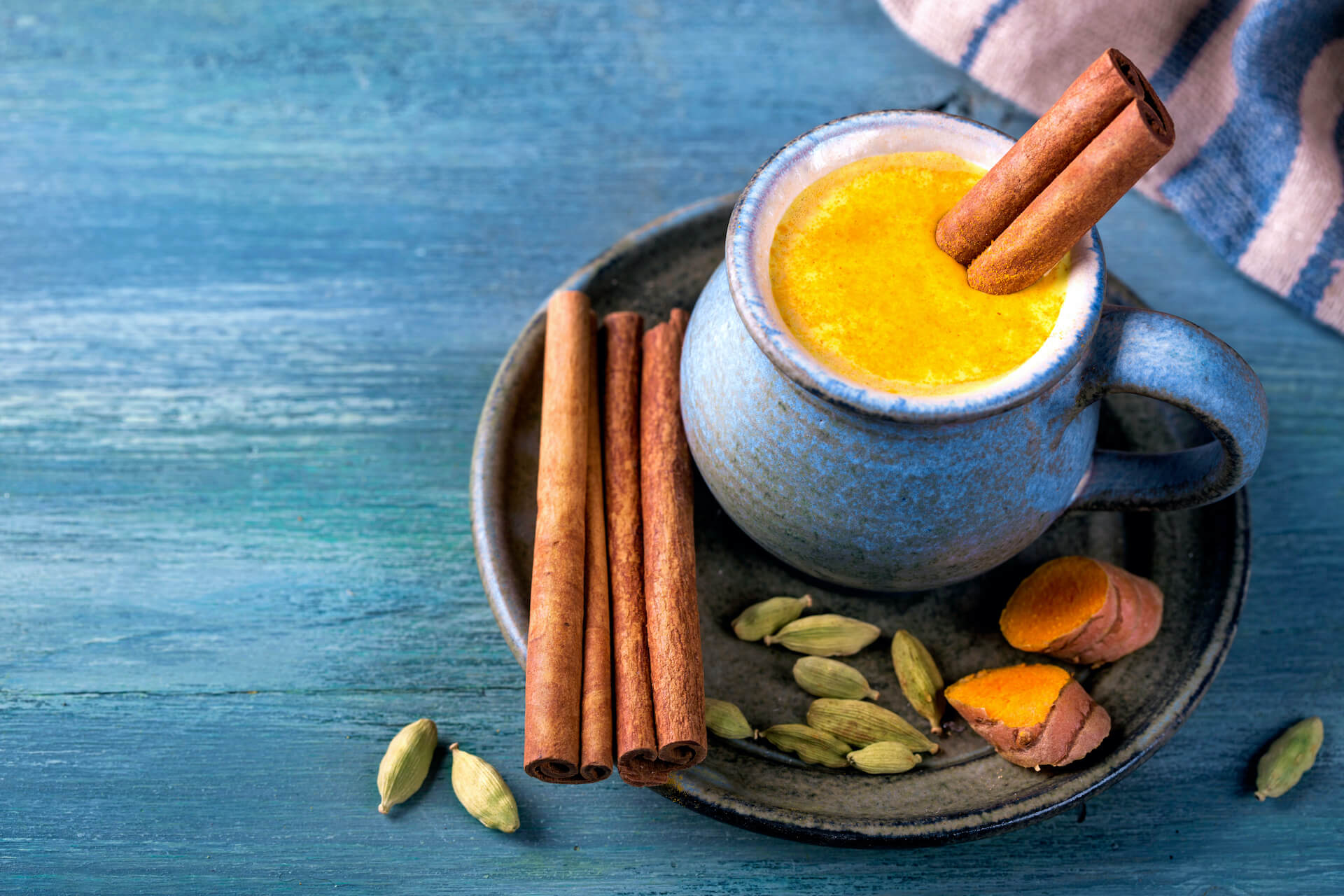 golden milk on a cup with turmeric root, seeds and cinnamon sticks on the side