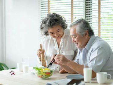 elder couple making a salad