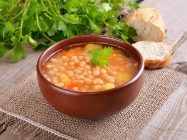 a bowl with white beans and a peace of bread on the side