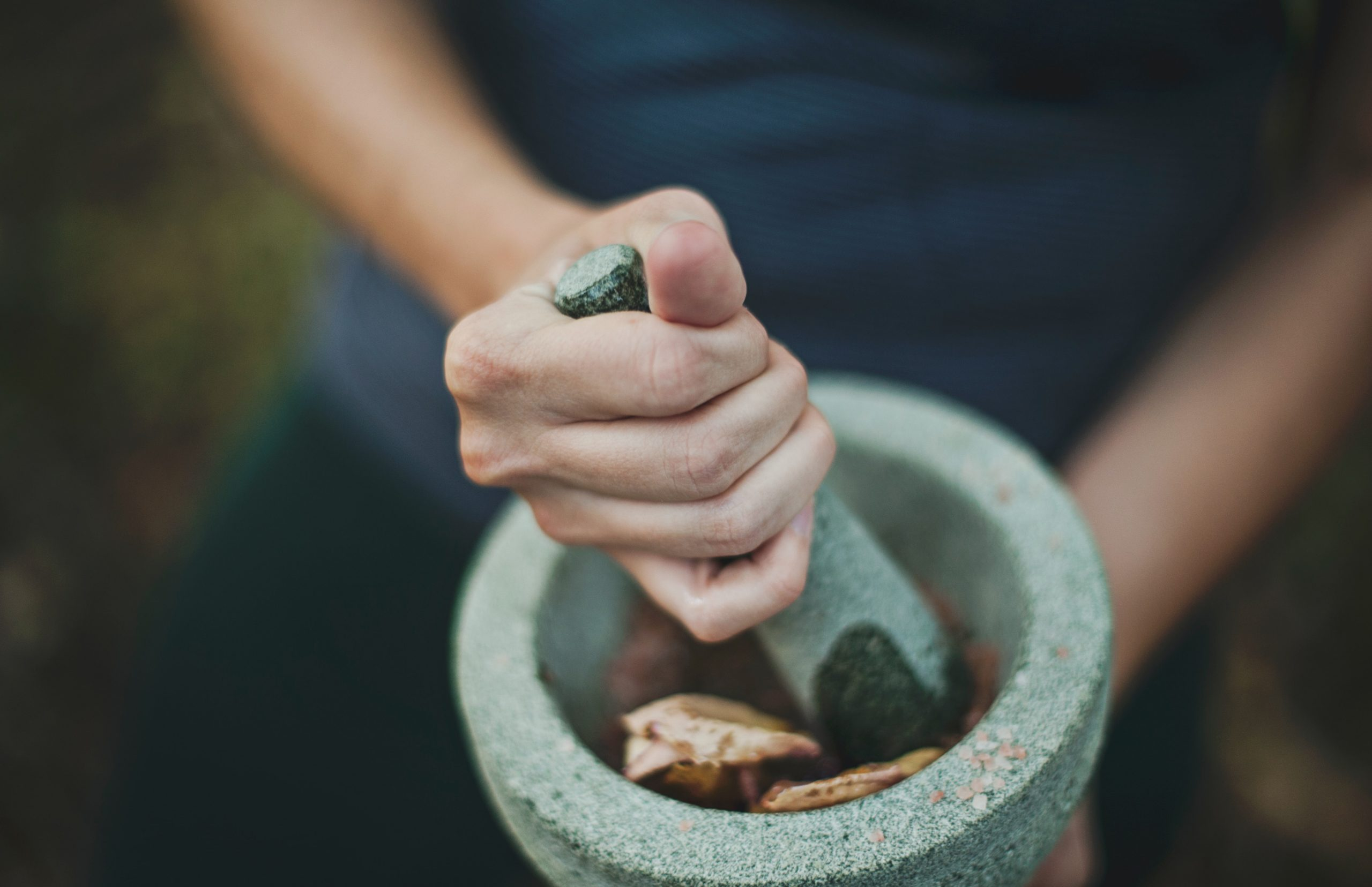 woman working on a herbal remedy on a morter