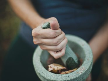 A woman's hands preparing a herbal remedy on a morter