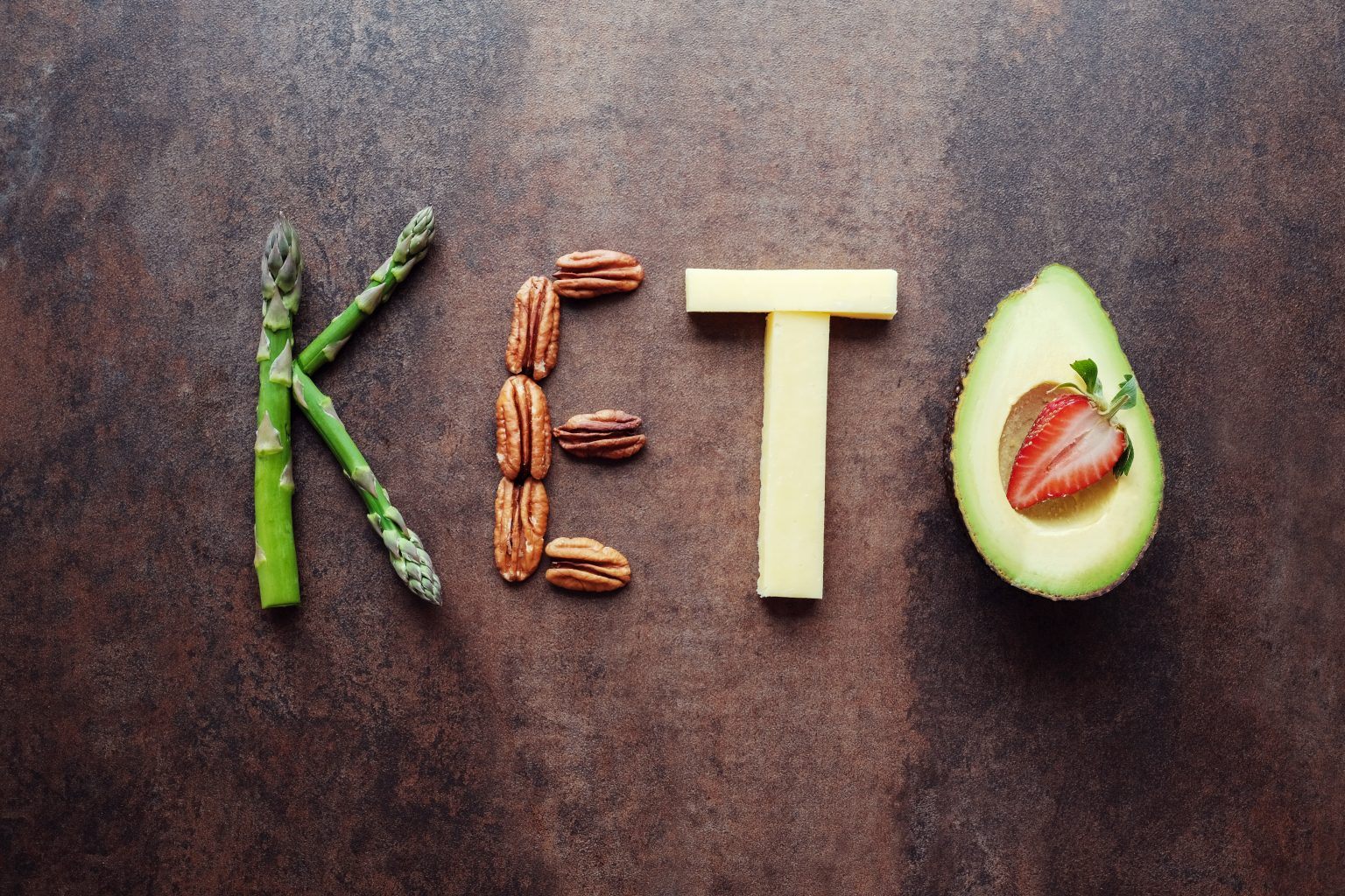 Keto word written with asparagus, nuts, cheese and avocado.
